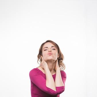 Giovane donna con apparenza accattivante morde le labbra sul fondale bianco