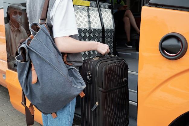 バスに入るバックパックとスーツケースを持つ若い女性