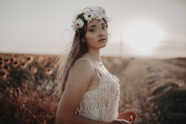 Young female with beautiful dress enjoying nature on the field
