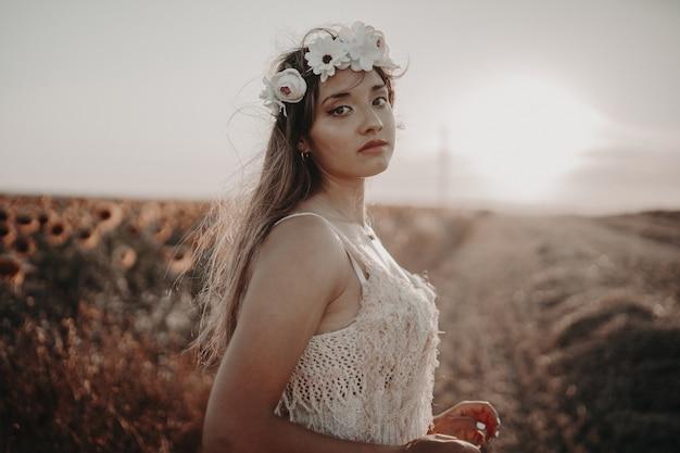 Молодая женщина в красивом платье, наслаждаясь природой на поле