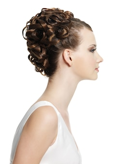 美しい短い巻き毛のヘアスタイルを持つ若い女性。白い壁の横顔の肖像画