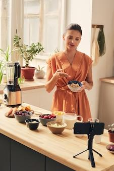 自家製スムージーのレシピを共有するカシューナッツのボウルを持つ若い女性
