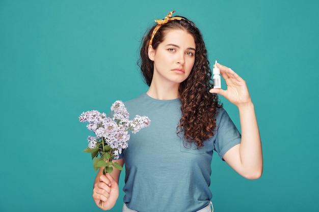 Молодая женщина с веткой сирени смотрит на вас и показывает небольшой пластиковый контейнер с эффективным противоаллергическим спреем для носа изолированно
