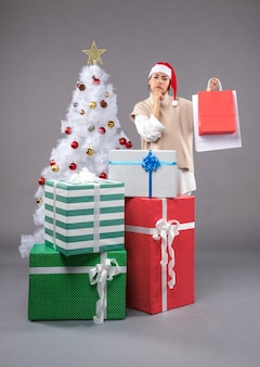 Young female with christmas presents on grey