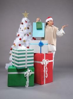 灰色のクリスマスプレゼントと若い女性