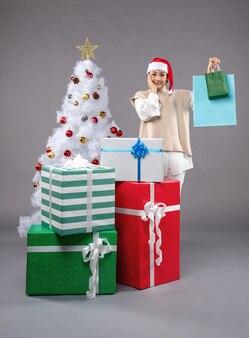 Молодая женщина с рождественскими подарками на сером
