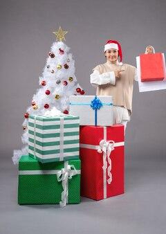 Молодая женщина с рождественскими подарками на свете