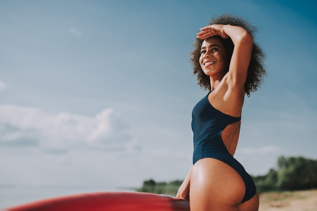 Young female with curly hair in swimsuit lean on surf.