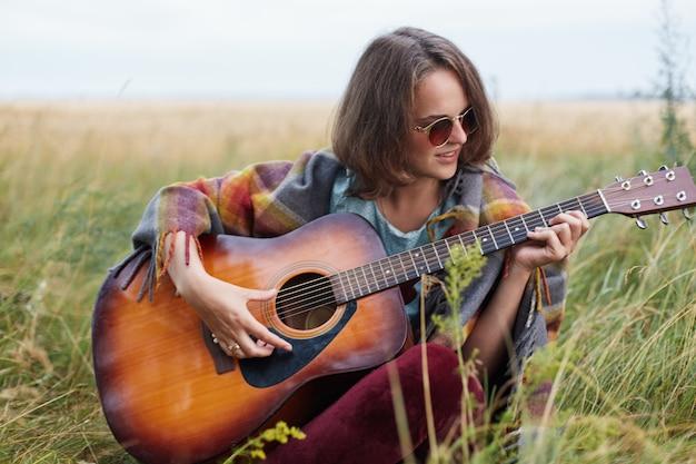 Молодая самка с темными короткими волосами сидит на зеленой траве и играет на гитаре, наслаждаясь красивыми пейзажами и поет свою любимую песню