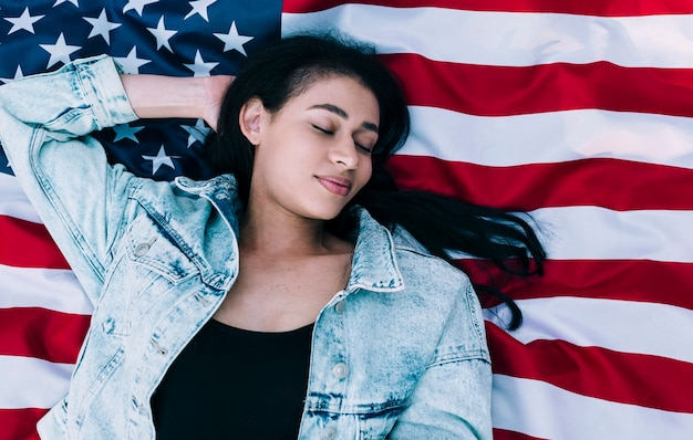 Young female with eyes closed lying on american flag