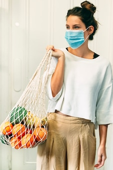 A young female with a face mask and a reusable mesh shopping bag full of fruits and vegetables
