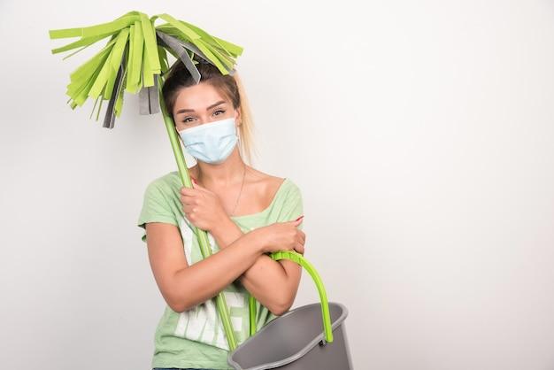 モップを保持しながら正面を見てフェイスマスクを持つ若い女性。