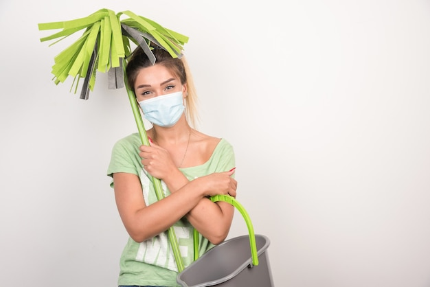 Young female with facemask looking at front while holding mop.