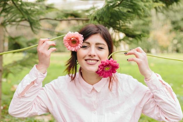 顔の近くの花を持つ若い女性