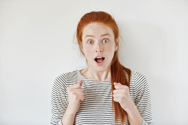 Молодая женщина с веснушками и рыжими волосами, связанная в хвостик, сжав кулаки, с выпученными глазами и широко открытым ртом, получает несколько положительных и неожиданных новостей с шокированным выражением лица