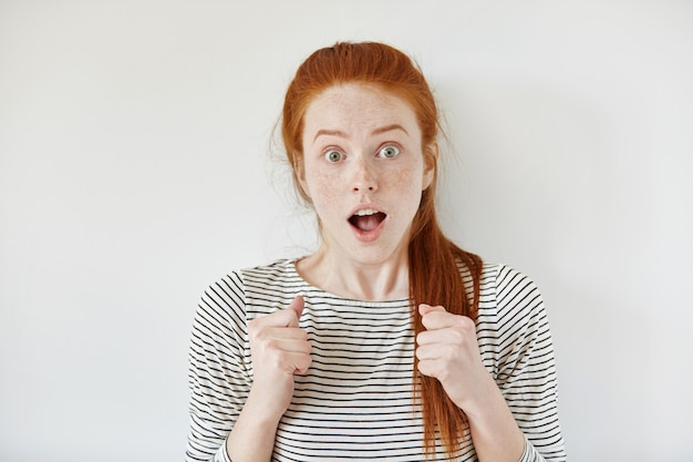 Young female with freckles and ginger hair, tied in ponytail clenching her fists, looking bug-eyed and keeping mouth wide open as receiving some positive and unexpected news, having shocked expression