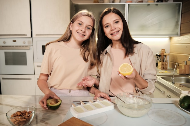 Young female with fresh lemon and her daughter with avocado looking at you while explaining how to prepare homemade icecream