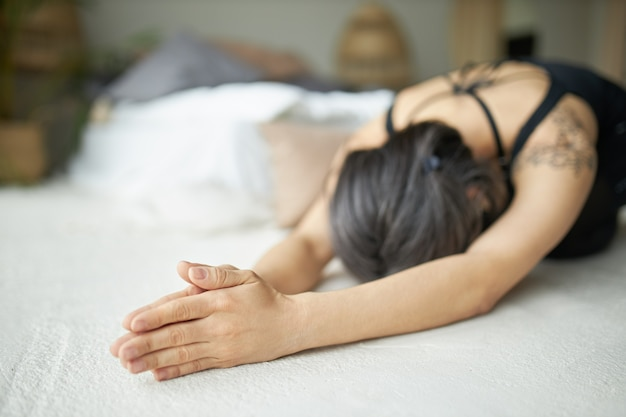 Молодая женщина с сероватыми волосами и татуировкой занимается йогой, растягивая тело