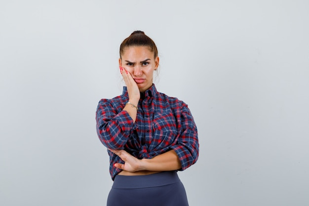 Young female with hand on cheek in checkered shirt, pants and looking thoughtful. front view.