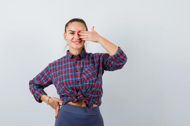 Giovane donna con la mano sull'occhio mentre tiene la mano sull'anca in camicia a scacchi, pantaloni e sembra felice. vista frontale.