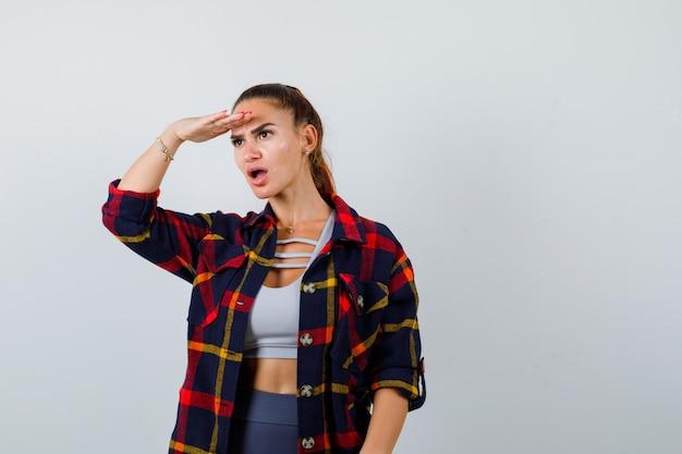 Giovane donna con la mano sulla testa per vedere chiaramente in crop top, camicia a scacchi, pantaloni e sguardo perplesso, vista frontale.
