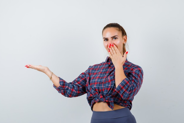 Giovane donna con la mano sulla bocca mentre mostra qualcosa in camicia a scacchi, pantaloni e sembra stupita. vista frontale.