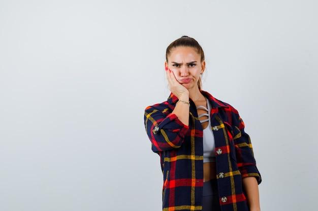 クロップトップ、市松模様のシャツ、物欲しそうに見える頬に手を持っている若い女性。正面図。