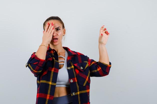 クロップトップ、市松模様のシャツ、困惑しているように見える、正面図でサイズのサインを表示しながら、目を手にした若い女性。