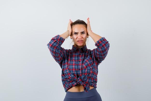 Giovane donna con le mani sulla testa in camicia a scacchi, pantaloni e sguardo smemorato. vista frontale.