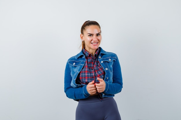 市松模様のシャツ、ジャケット、パンツを着て、元気そうに見える彼女の前に手を持っている若い女性。正面図。