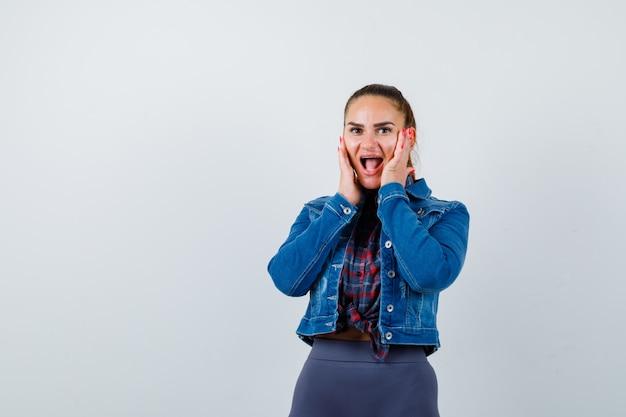 市松模様のシャツ、ジャケット、パンツで頬に手を当てて、驚いて見える若い女性。正面図。