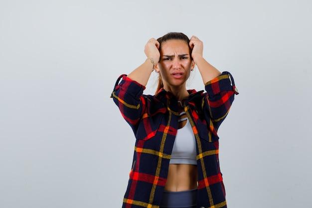 クロップトップ、市松模様のシャツ、ズボンで頭に手を置いて、忘れて見える若い女性。正面図。
