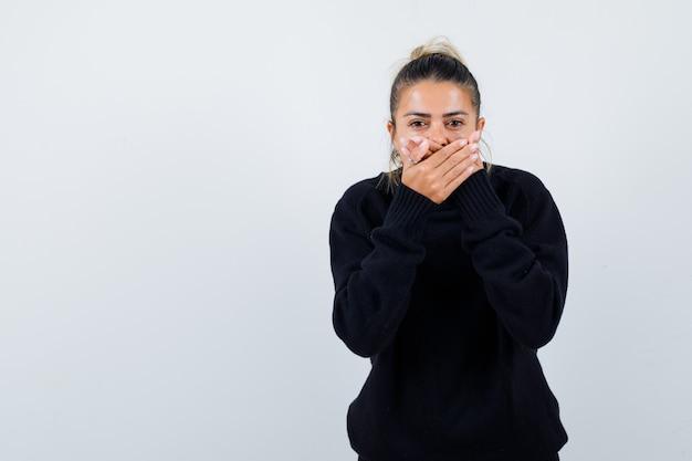 Молодая женщина с руками за рот в свитере с высоким воротом и выглядит озадаченным. передний план.