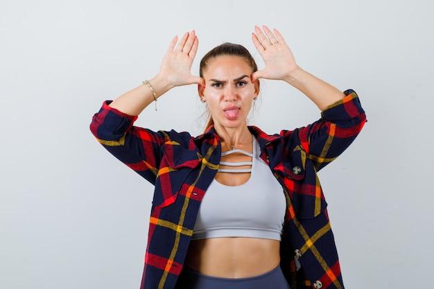 머리 위로 손을 머리 위로 귀로 삼고 작물 상의, 체크 무늬 셔츠, 바지를 입은 젊은 여성, 그리고 재미있고 앞모습을 보고 있습니다.