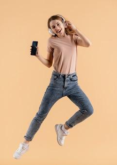 ヘッドフォンとモバイルジャンプを持つ若い女性
