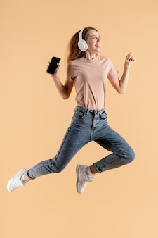 Young female with headphones and mobile jumping