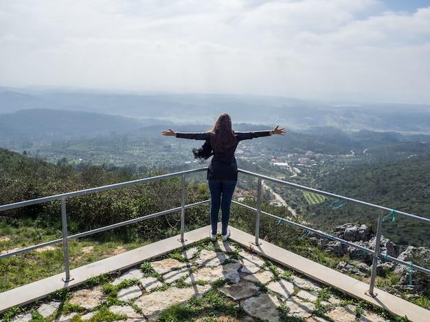 山の美しい景色を楽しみながら両手を広げて若い女性