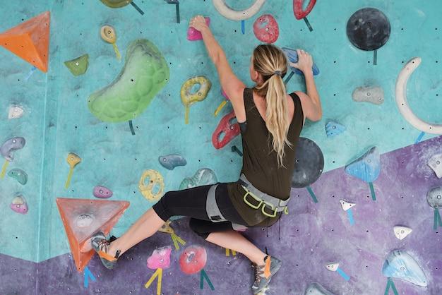 Молодая женщина с хвостиком цепляется за искусственные камни во время скалолазания в одиночестве в тренажерном зале или развлекательном центре