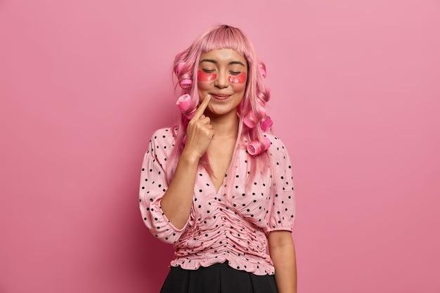 깨끗한 피부를 가진 젊은 여성, 안색 관리, 검지 손가락을 입술 근처에 유지, 눈을 감고, 회춘을위한 패치 적용