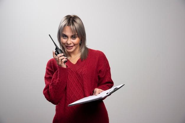라디오 트랜시버와 클립보드가 회색 배경에 포즈를 취하는 젊은 여성.