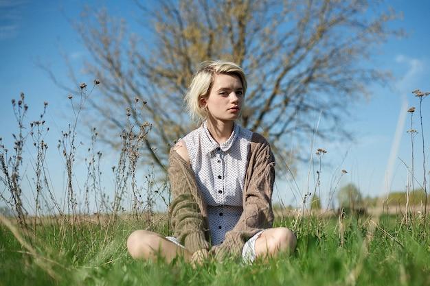 晴れた日にフィールドで地面に座っている斑点のあるドレスとセーターの短い髪の若い女性