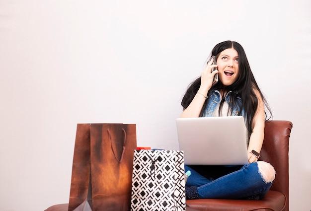 Молодая женщина со смартфоном и ноутбуком, делающим покупки в интернете дома, изолировала белую поверхность