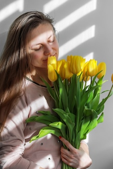 Young female with yellow flowers tulip natural portrait lifestyle near white