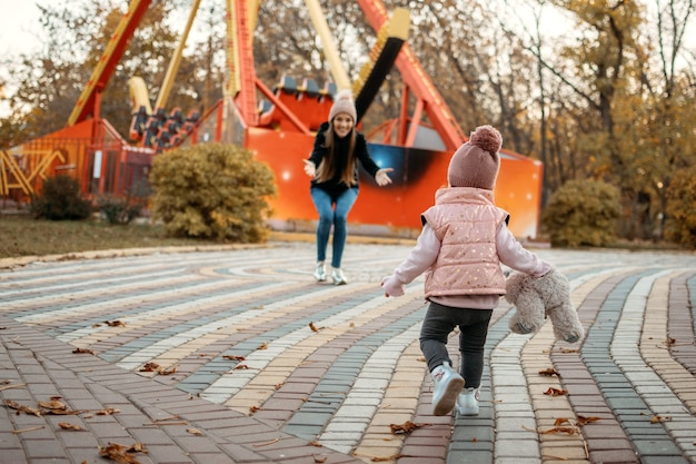 Young female woman babysitter and toddler baby girl walk in autumn park happy family mom and toddler