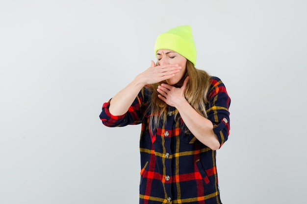Giovane donna in una camicia a scacchi con un cappello