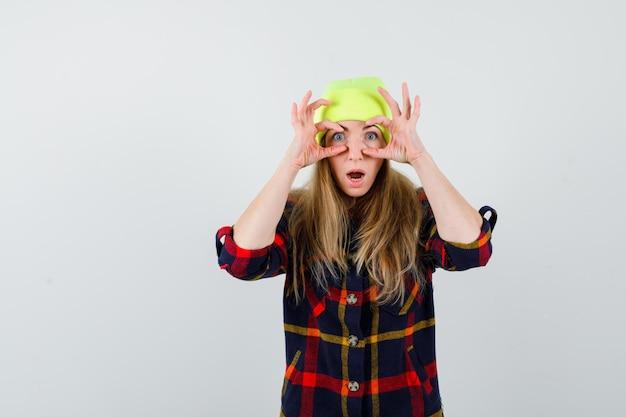 帽子と市松模様のシャツを着た若い女性