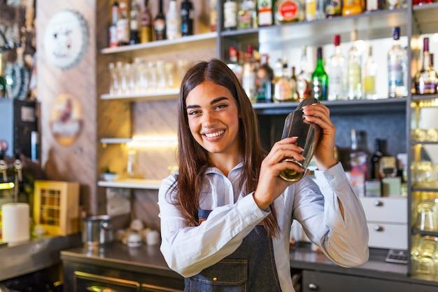Young female worker at bartender desk in restaurant bar preparing cocktails with shaker.