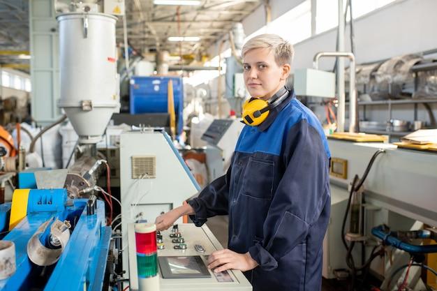 작업복을 입은 젊은 여성 노동자가 산업 기계의 제어판 앞에 서서 작업 준비를 하는 동안 당신을 보고 있습니다