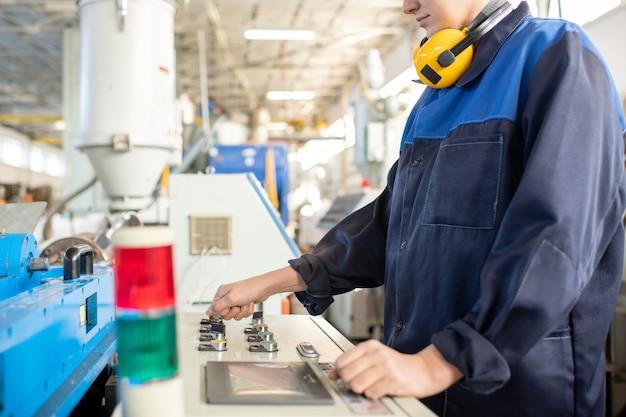 작업복을 입은 젊은 여성 노동자가 산업 기계의 제어판 앞에 서서 작업을 준비하는 동안 손잡이를 돌립니다.