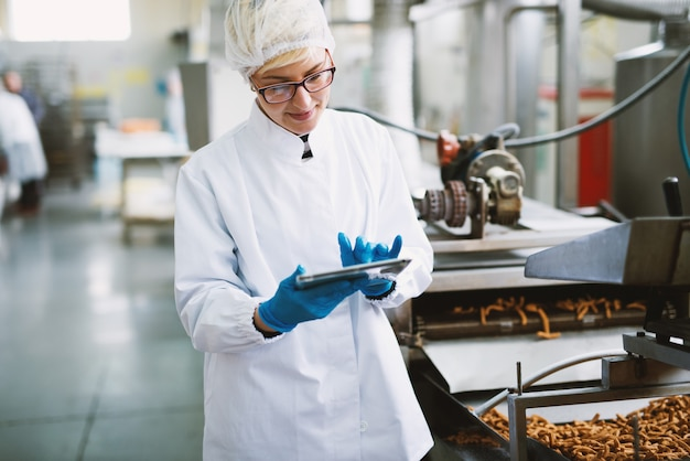 Молодая работница в стерильной одежде проверяет качество продукции в пищевой фабрике.